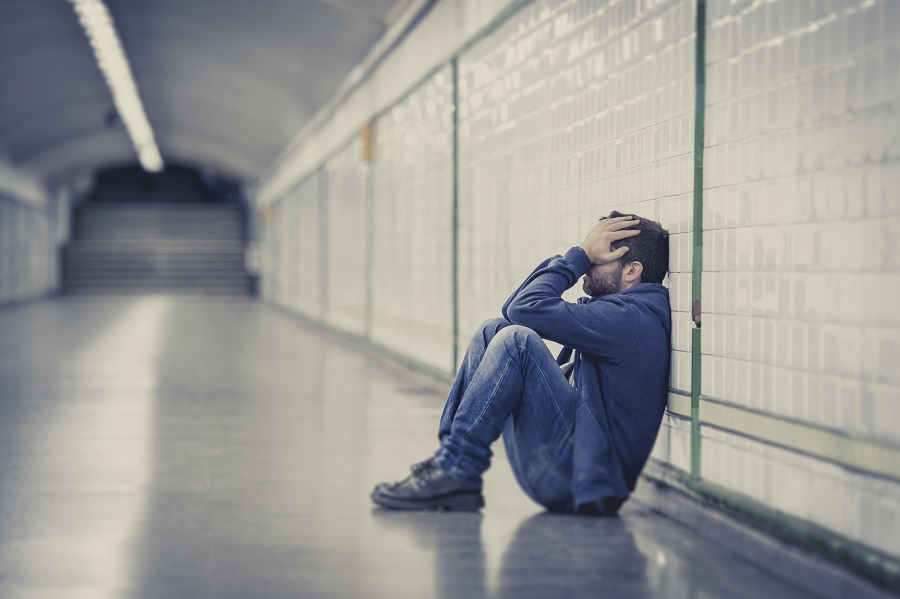 Young sad man sick and depressed sitting on ground street tunnel